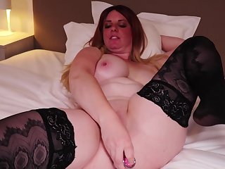 Curvaceous blonde woman, Axxelle is enervating black stockings and getting a sex toy up her fundamentally